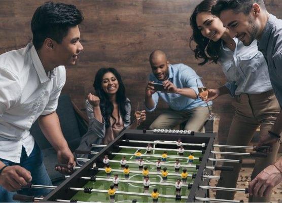 gente de un club jugando al futbolin